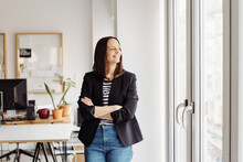 Happy Smiling Businesswoman Looking Out Of A Bright Window