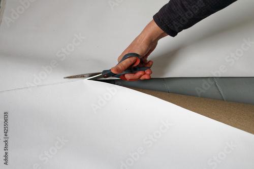Fototapeta Cięcie płótna na podobrazia. Ręka kobiety z nożyczkami, które kroją płótno. obraz