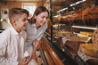 Charming young boy shopping for desserts with his mom at the bakery, copy space
