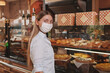 Woman looking to the camera, shopping at the bakery store, wearing medical face mask, copy space