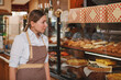 Lovely female baker walking at her bakery store, looking at pastry on the display, copy space