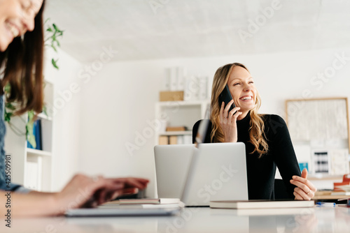 Two businesswoman laughing in amusement as one chats on her mobile phone Wallpaper Mural