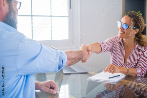 Smiling caucasian female hr manager handshake hire male candidate at job interview make good first impression, happy mixed race client shake hand of bank broker, respect, business agreement concept.