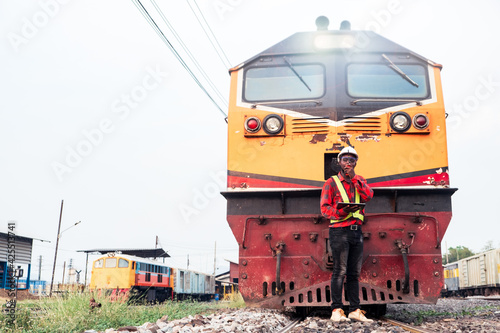 African engineer control a the train on railway with using tablet and talking by radio communication or walkie talkie