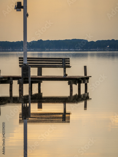 A bench on a jetty with the evening sun shining through the clouds, and a view at the Steinhuder Meer in Fluegelhorst, Lower Saxony, Germany