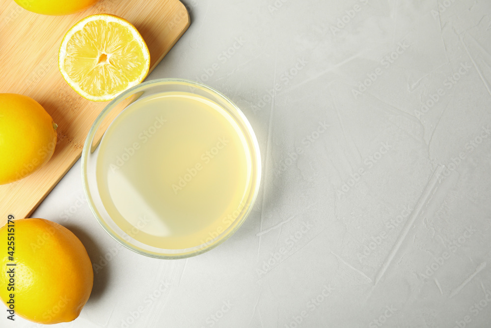 Fototapeta Freshly squeezed juice and lemons on light table, flat lay. Space for text