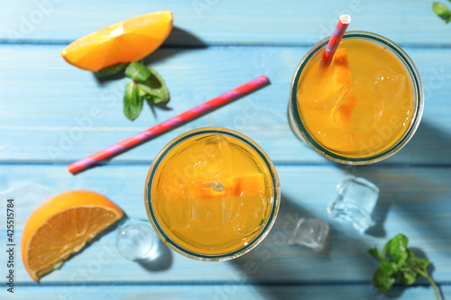 Delicious orange soda water on light blue wooden table, flat lay