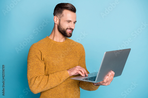 Obraz Portrait of nice attractive focused cheerful guy employee using laptop programming isolated over bright blue color background - fototapety do salonu