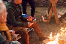 Grilling Sausages Over A Campfire, Campers Roasting Sausages On Toasting Forks. Fire Place, Friends, Tourists Are Sitting Near The Flame.