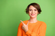 Leinwandbild Motiv Photo of positive happy young woman point finger empty space feedback promoter isolated on green color background