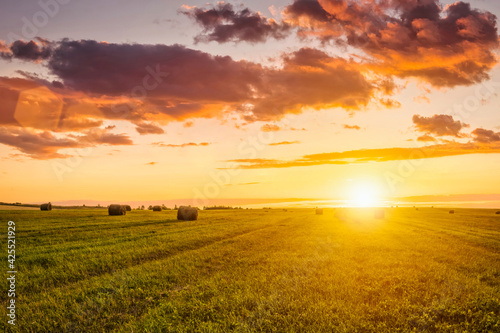 Photo Sunset in a field with haystacks on a summer or early autumn evening with a cloudy sky in the background