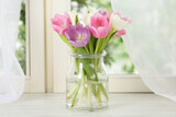 Beautiful fresh tulips on window sill indoors. Spring flowers