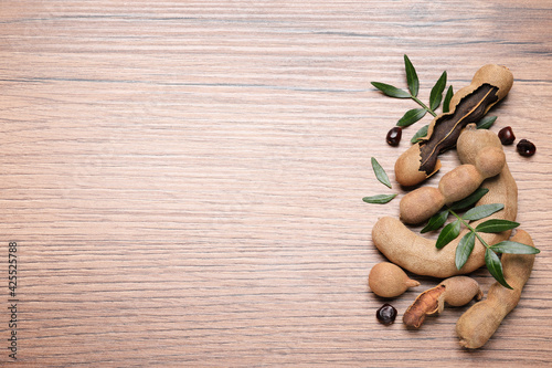 Delicious ripe tamarinds and leaves on wooden table, flat lay. Space for text