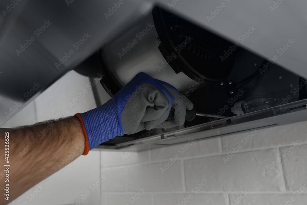 Fototapeta Worker repairing modern cooker hood indoors, closeup