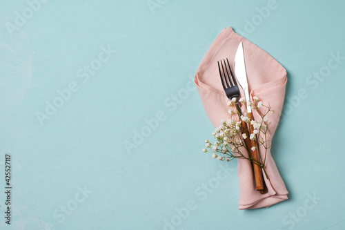 Obraz Tableware setting with fork, knife, napkin and flower on blue background, - fototapety do salonu
