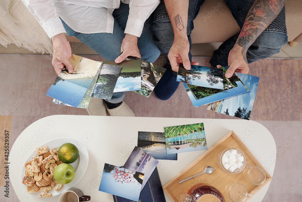 Fototapeta Hands of mother and adult son drinking tea with sugar cookies and looking at printed old photos of nature, view from above - obraz na płótnie