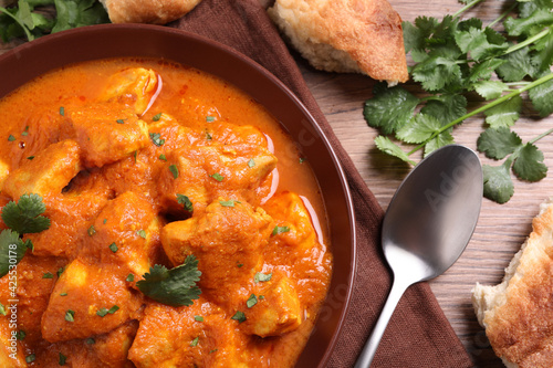 Obraz Bowl of delicious chicken curry on wooden table, flat lay - fototapety do salonu