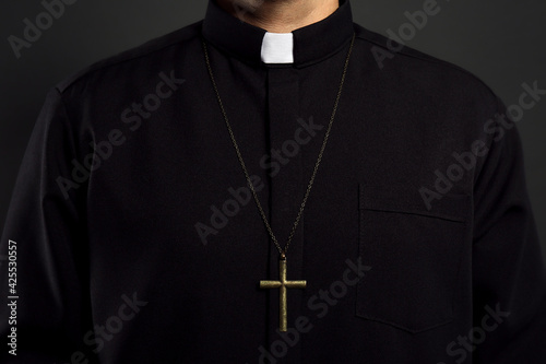 Priest with cross on black background, closeup Fototapeta
