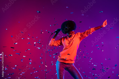 Photo of funky crazy lady dance hold mic confetti fall wear sweatshirt sunglass isolated gradient neon background