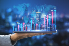 Business Development Concept With Digital Tablet On Human Palm With Glowing Night Megapolis City Skyline And Vertical Blue And Pink Growing Arrows On World Map With Financial Graphs Background