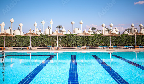 Fotografia Beach with beach chairs, thatched umbrellas near the pool in Egypt