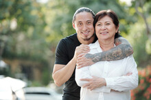 Portrait Of Handsome Mixed-race Adult Man Hugging His Mature Mother From Behind And Smiling At Camera When They Are Standing Outdoors