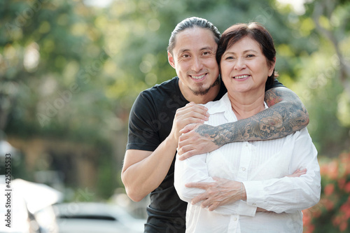 Obraz Portrait of handsome mixed-race adult man hugging his mature mother from behind and smiling at camera when they are standing outdoors - fototapety do salonu
