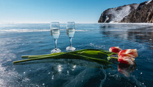 On A Blue Transparent Frozen Lake There Are Two Glasses Of Champagne, Red And Yellow Tulips. Cracks And Reflections On Mirror Ice. Background - Azure Sky, Picturesque Rocks. Baikal