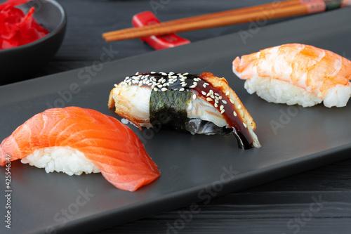 Nigiri sushi with salmon, eel and prawn served on black ceramic plate