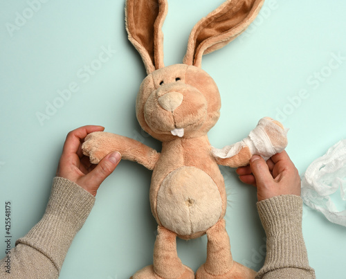 Foto soft plush rabbit with a bandaged paw with a white medical bandage