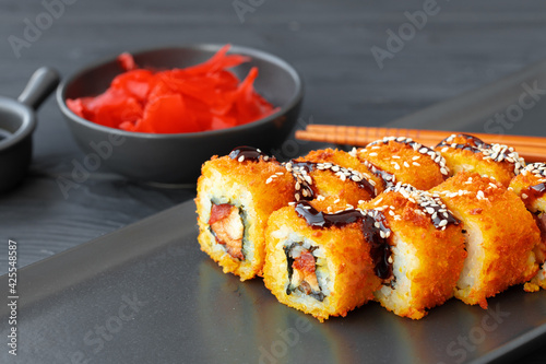 Sushi roll fried in tempura on black plate