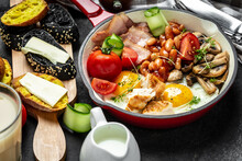 English Breakfast With Fried Eggs, Bacon, Mushrooms, Chicken Fillet, Beans, Toasts And Fresh Salad. Food Recipe Background. Close Up