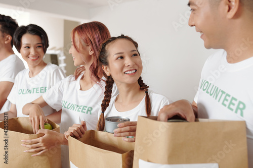 Fotografie, Obraz Pretty young smiling woman volunteering with her friends at donation center and