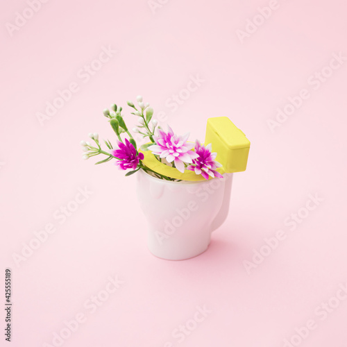 Pink and white flowers in white toilet. Pink background. Fototapete