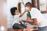 Cheerful African American Man and little boy having fun laughing with shaving foam on their faces in bathroom at home together.