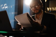 Male Businessman Works With Business Reports And Financial Charts. Paperwork Late At Night