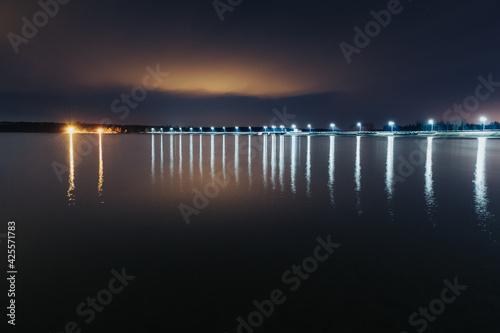 Fototapeta Nocne odbicia latarni w wodzie jeziora. obraz
