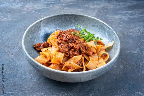 Modern Style traditionelle italienisches Ragu alla Bolognese Sauce mit with Papedelle Pasta Nudeln noodles und Parmesan Käse serviert als close-up in einer Keramik Design Schale mit Textfreiraum