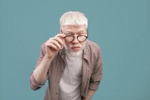 Poor Eyesight. Albino Man In Eyeglasses Squinting Eyes, Having Bad Sight, Trying To See Something Over Blue Background