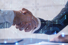 Handshake Of Two Businessmen Who Enters Into The Contract To Develop A New Software To Improve Business Service At A Company. Technological Icons Over The Table With The Document.