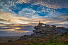Person Standing On Top Of Rocky Outcrop At Sunset. Stowes Hill, Cornwall