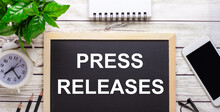 PRESS RELEASES Written On A Black Background Near Pencils, A Smartphone, A White Notepad And A Green Plant In A Pot