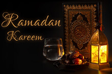Ramadan Kareem, Muslim Religious Tradition, Holy Month Of Islam And Iftar Concept Theme With A Bowl Of Dates, Prayer Beads, Glass Of Water, Quran And Arabic Lantern On Black Background