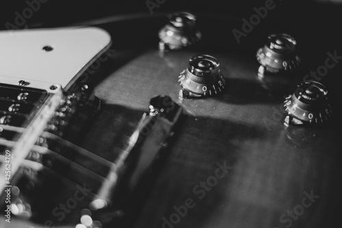 Czarno białe zdjęcie, zbliżenie na gitarę. Struny i przełączniki - detale instrumentu muzycznego