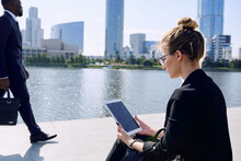 Young Blond Elegant Businesswoman In Formalwear Using Tablet While Sitting By Riverside In Urban Environment With Man Passing By