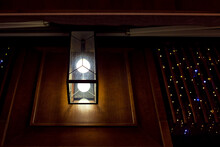 Square Glass Lantern With Light Bulb On Wooden Wall Of Retro Architecture Building Facade, Night City Scene Close-up.
