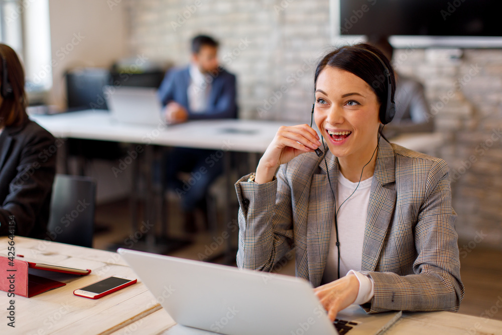 Fototapeta Beautiful female customer service talking on the headset with client and smiling