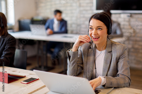 canvas print motiv - djile : Beautiful female customer service talking on the headset with client and smiling