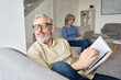 Leinwandbild Motiv Happy older senior man husband wearing glasses reading book relaxing sitting on couch at home with mature wife using laptop. Middle aged family couple enjoying casual daily activities