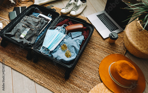 Packing suitcase for travel vacation in new normal Fototapeta